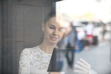 young woman working, communicating with tablet, drinking coffee in cafe, view through glass, nice reflection, bokeh blur, city life reflected