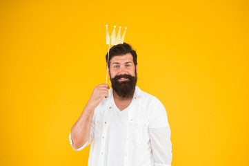 Birthday boy. Guy in yellow background posing with booth props. Photo booth fun. Bearded man king costume party. Handsome bearded guy king. King of party. Costume party. Holiday carnival celebration