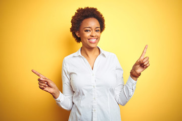 African american business woman over isolated yellow background smiling confident pointing with...