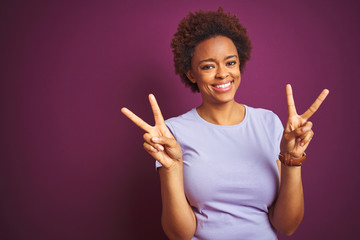 Young beautiful african american woman with afro hair over isolated purple background smiling looking to the camera showing fingers doing victory sign. Number two.
