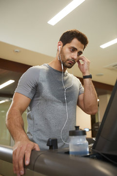 Waist up portrait of sweaty young man listening to music while running on treadmill in gym
