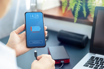 Woman charges her smartphone with power bank using fast charge  USB-C cable. Interface on the screen was created in graphic program.
