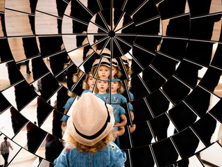 Girl's reflection in many mirrors arranged in a parabolic shape. Multiple points of view, multiple angles. Fragmented multi-faceted portrait. Mirror array.