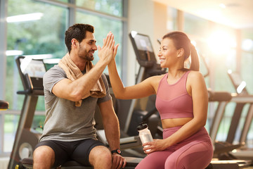 Portrait of beautiful sportive couple high five during workout in gym, copy space Wall mural