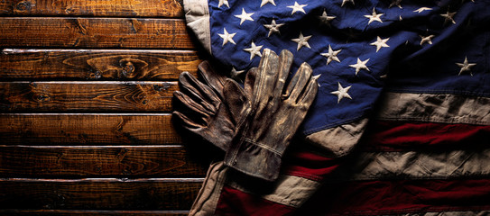 Old and worn work gloves on large American flag - Labor day background Fotomurales