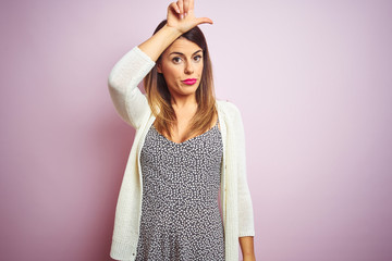 Young beautiful woman standing over pink isolated background making fun of people with fingers on forehead doing loser gesture mocking and insulting.