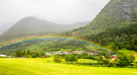 Colorful rainbow over the fields, lake and houses of Skei village, Jølster in Sogn og Fjordane county, Norway.