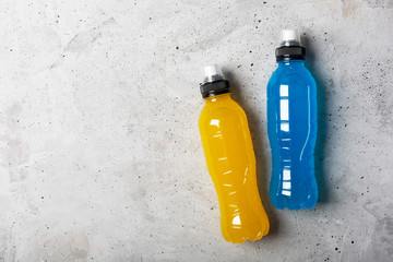 Fototapeta Isotonic energy drink. Bottles with blue and yellow transparent liquid, sport beverage on a gray concrete background obraz