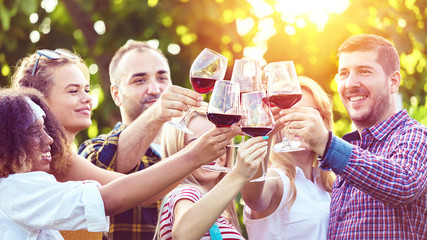 Happy multi-ethnic friends having fun together in restaurant outdoor vineyard toasting and drinking red wine