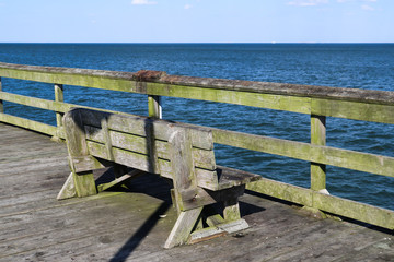 A lone bench on the Ocean View fishing pier in Norfolk, Virginia.