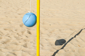 A blue ball and yellow pole on the beach for playing tetherball.