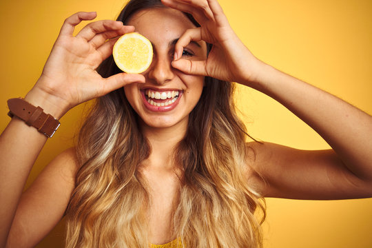 Young beautiful woman holding a lemon on eye over yellow isolated background with happy face smiling doing ok sign with hand on eye looking through fingers