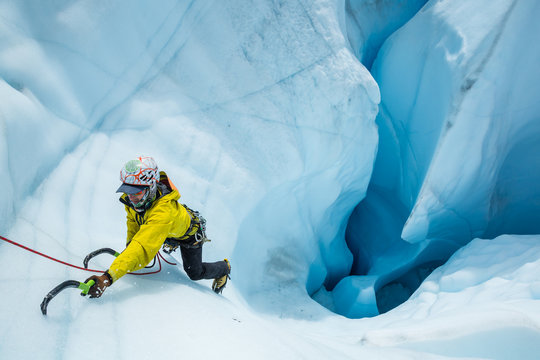 Ice climber expertly ascending out of a massive mouin in the Matanuska Glacier