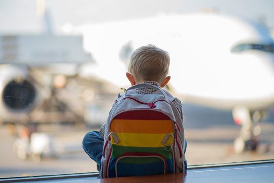 Young boy sitting looking out of the window at the airport anxiously waiting for the plane