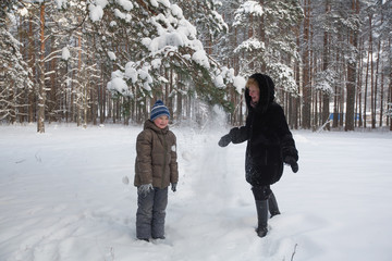 Young woman playing with a his son in a snowy winter Park.