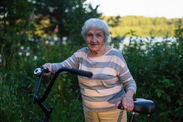 Elderly woman with bike an outdoor. Pensioner's bicycle ride.