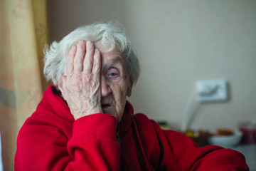 An old woman in a red jacket covers one eye with her hand.