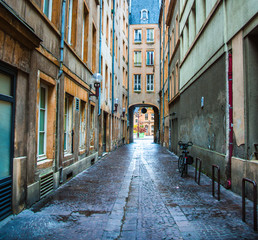 Aluminium Prints Narrow alley Colorful empty narrow cobblestone alley through old buildings to archway