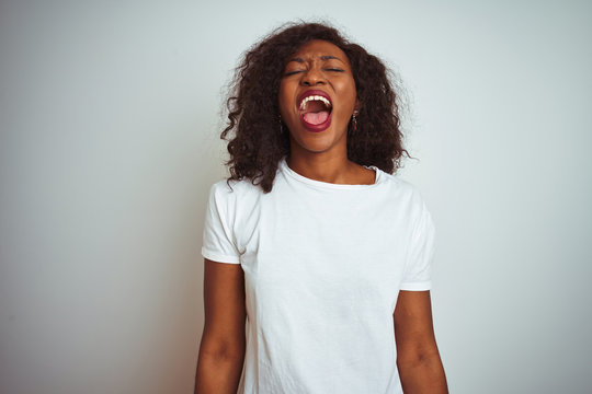 Young african american woman wearing t-shirt standing over isolated white background angry and mad screaming frustrated and furious, shouting with anger. Rage and aggressive concept.