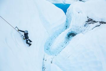 Ice climber over deep blue pool on the Matanuska Glacier in Alaska. Woman climber on steep terrain roped up.