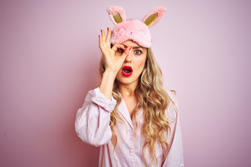 Young beautiful woman wearing pajama and sleep mask over pink isolated background doing ok gesture...