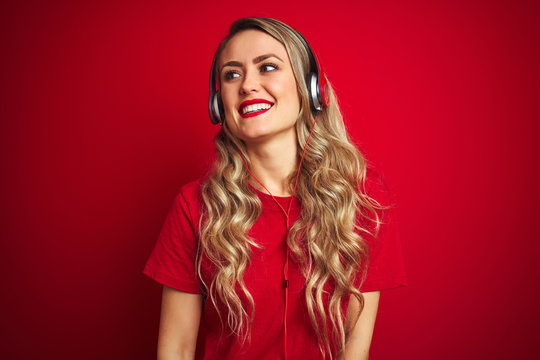 Young beautiful woman wearing headphones over red isolated background looking away to side with smile on face, natural expression. Laughing confident.