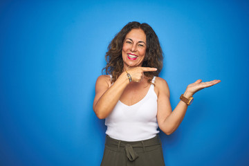 Middle age senior woman with curly hair standing over blue isolated background amazed and smiling...