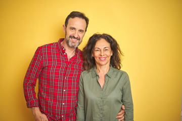 Wall Mural - Beautiful middle age couple over isolated yellow background with a happy and cool smile on face. Lucky person.