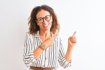 Middle age businesswoman wearing striped dress and glasses over isolated white background smiling...