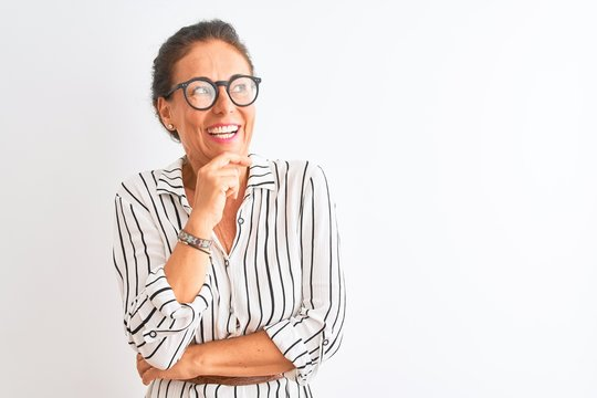 Middle age businesswoman wearing striped dress and glasses over isolated white background with hand on chin thinking about question, pensive expression. Smiling and thoughtful face. Doubt concept.
