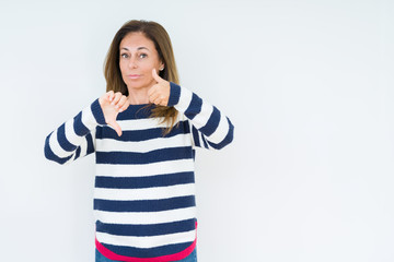 Beautiful middle age woman wearing navy sweater over isolated background Doing thumbs up and down,...
