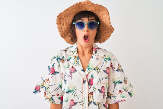 Woman on vacation wearing summer hat shirt and sunglasses over isolated white background scared in shock with a surprise face, afraid and excited with fear expression