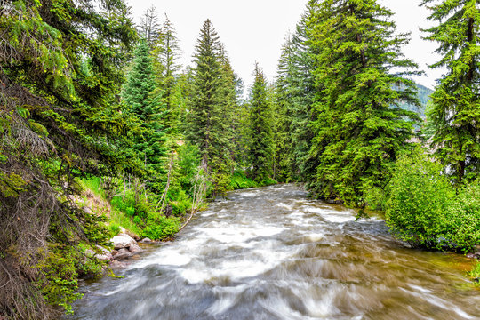 Vail resort town city in Colorado with long exposure of Gore creek river and pine trees