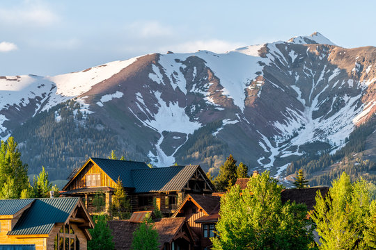 Mount Crested Butte Colorado village houses in summer with colorful sunset on green trees and lodging