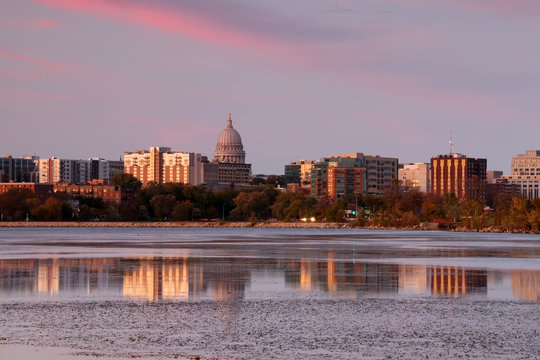 Beautiful cityscape during autumn sunset. Madison downtown skyline with Wisconsin State Capitol building dome across lake Monona bay. Buildings and bright colors sky reflected in the water.