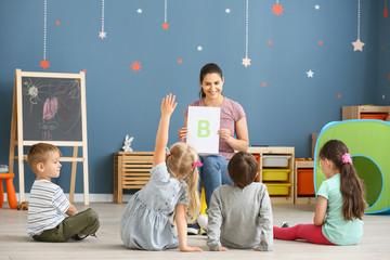 Cute little children learning letters in kindergarten Wall mural