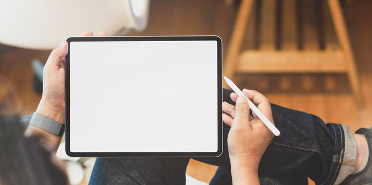 Young male freelancer holding blank screen tablet