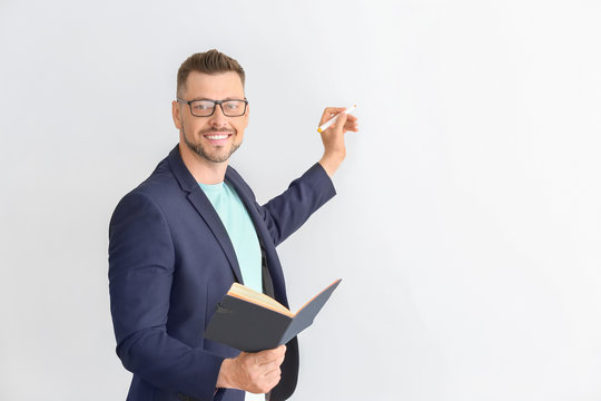Handsome male teacher writing something on light background