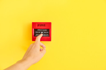 Woman using manual call point of fire alarm system