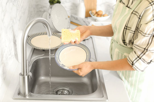 Woman washing dishes in kitchen sink