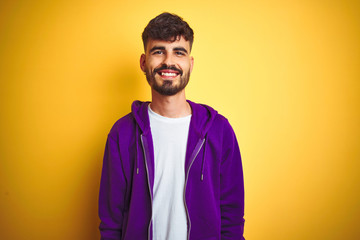 Young man with tattoo wearing sport purple sweatshirt over isolated yellow background with a happy...