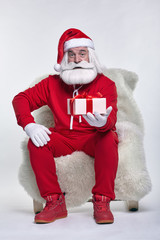 Portrait of a Santa Claus in sportsware sitting in a chair covered with sheepskin with gift box in hands