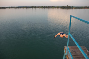 man jumping from tower at lake water on sunset