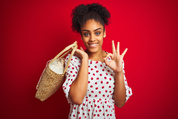 African american woman wearing fashion dress holding wicker bag over isolated red background doing ok sign with fingers, excellent symbol