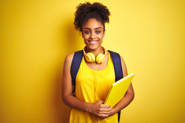 Afro woman using backpack and headphones holding notebook over isolated yellow background with a...