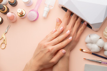 Poster de jardin Manicure Nail care. beautiful women hands making nails painted with pink gentle nail polish on a pink background. Women's hands near a set of professional manicure tools. Beauty care