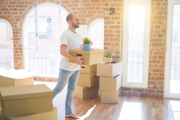 Young handsome man moving to a new house, holding cardboxes smiling very happy for new apartment