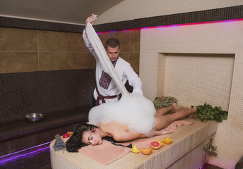 A beautiful girl with dark hair and a slender figure takes bath procedures in a Hammam, a bath attendant does massage, applies cosmetic oils and means to the skin of a slender young girl