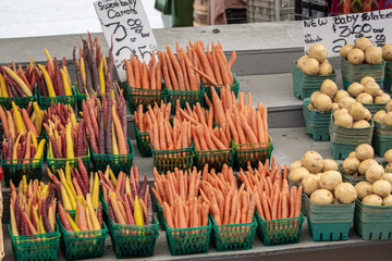 A vendor's stall in a farmer's market offers carrots and potatoes in its display.