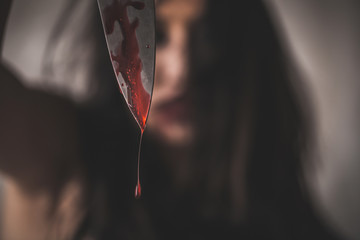Close up bloody knife of horror female assassin with scary face on black background, Depression and fear.